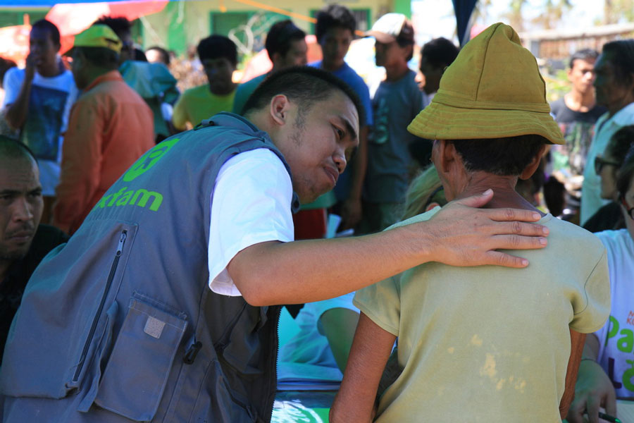 Vincent malasador gives support and reassurance to recipient during the distribution of hygiene items in North Cebu, after Haiyan Typhoon hit the Philippines (November 2013). Credit: Jane Beesley/Oxfam
