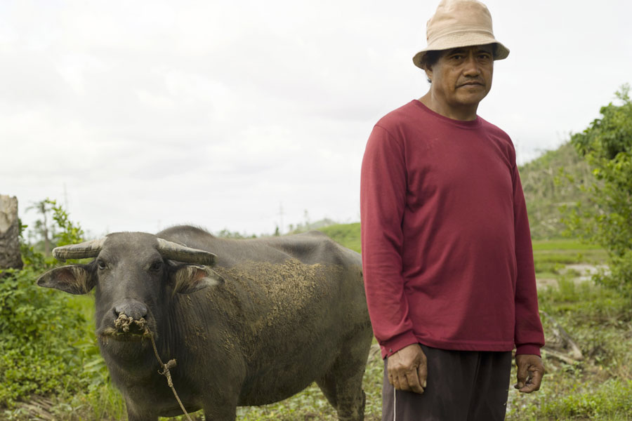 Rice and Coconut Farmer, Gistado Gallaron stands in his rice field in Tanauan, Leyte. Photo: Simon Roberts/Oxfam