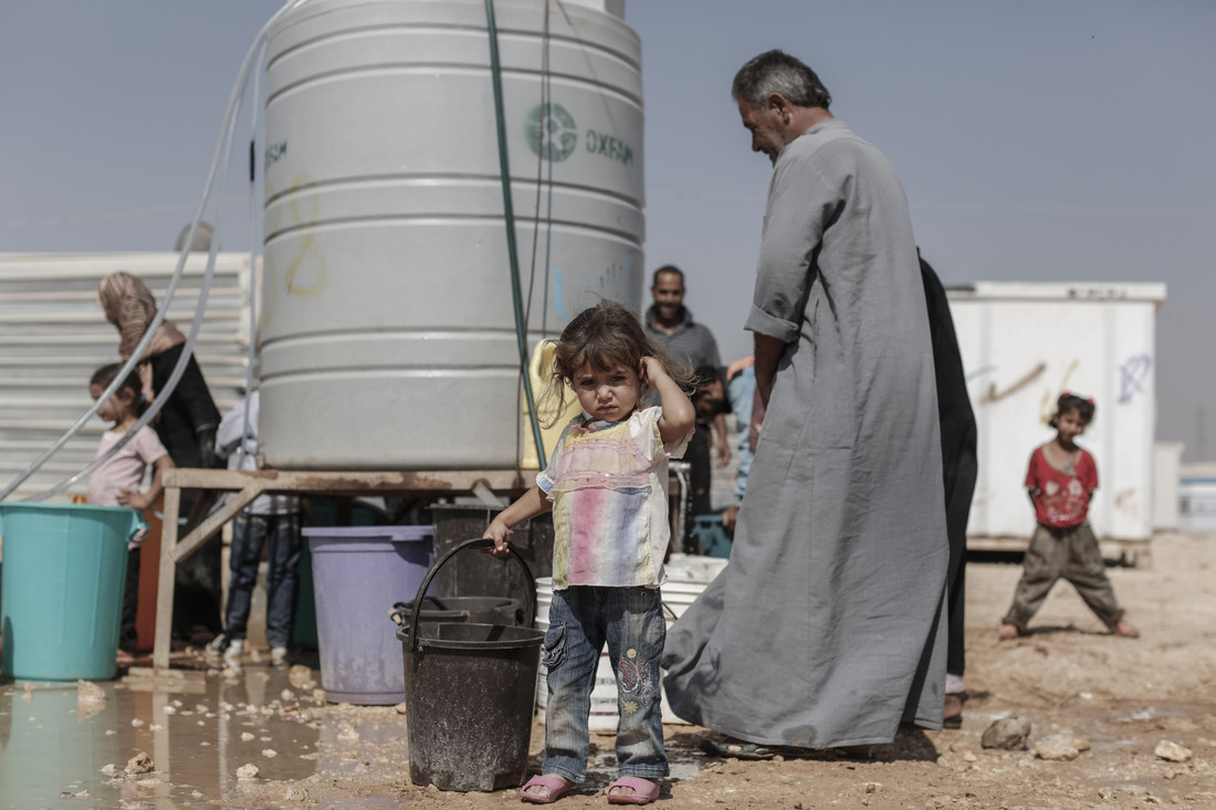 Tala, 2, from Ghouta, near Damascus in Syria, waits as her father collects drinking water from an Oxfam supplied water tank in Zataari camp in Jordan. Photo credit: Sam Tarling / Oxfam