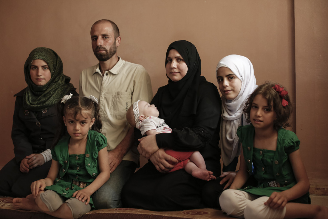 L-R Amira, 15, Rasha, 7, Ahmad, Thakaa, Reem, 6-months, Zeinah 14, and Sara, 11 sit in their apartment in Zarka, Jordan, on September 8, 2015. Photo credit: Sa