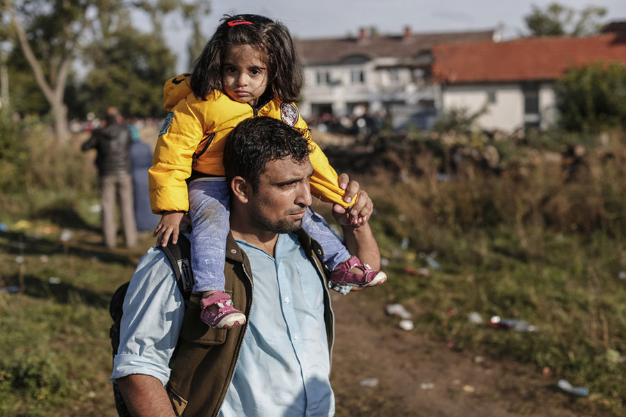 A father and his daughter, both refugees, walk towards a registration centre for migrants to get travel permits in Serbia