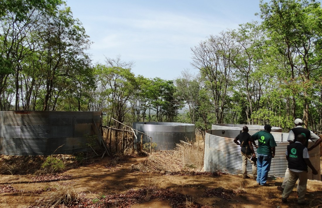 Oxfam staff inspect water tanks in Nduta refugee camp.