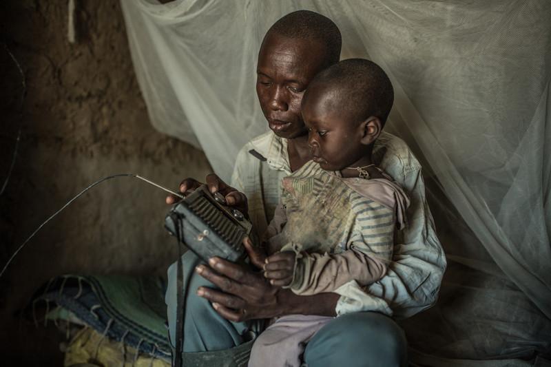 Nabonswendé junto a su hijos escuchando la información meteorológica por la radio