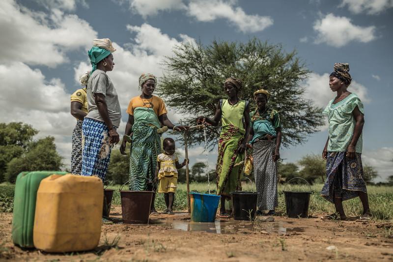 Noaga Ouèda (derecha) junto con otras mujeres de su comunidad recogiendo agua potable de un grifo que se alimenta de la torre de agua que han instalado en su comunidad y que funciona con energía solar.