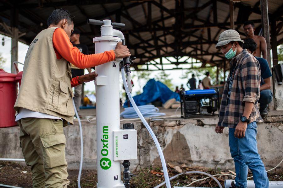 L'équipe Eau, assainissement et hygiène d'Oxfam achemine du matériel de filtration SkyHydrant, qui permet de traiter les eaux souterraines sans électricité ni produits chimiques. Une unité peut potabiliser 1 200 litres d'eau tirée d'un puits de captage par heure, ce qui correspond aux besoins journaliers de 500 personnes. (Photo : Hariandi Hafid/Oxfam)