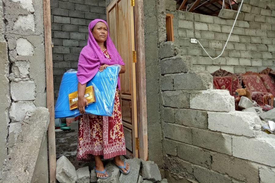 Oxfam et ses partenaires ont distribué près de 500 bâches et 400 pièces d'étoffe appelées sarong aux survivants de Dampal. « Je remercie Oxfam pour la bâche et le sarong. Je veux monter la tente devant ma maison pour pouvoir plus facilement faire la cuisine à côté. » (Photo : Irwan Firdaus/Oxfam)