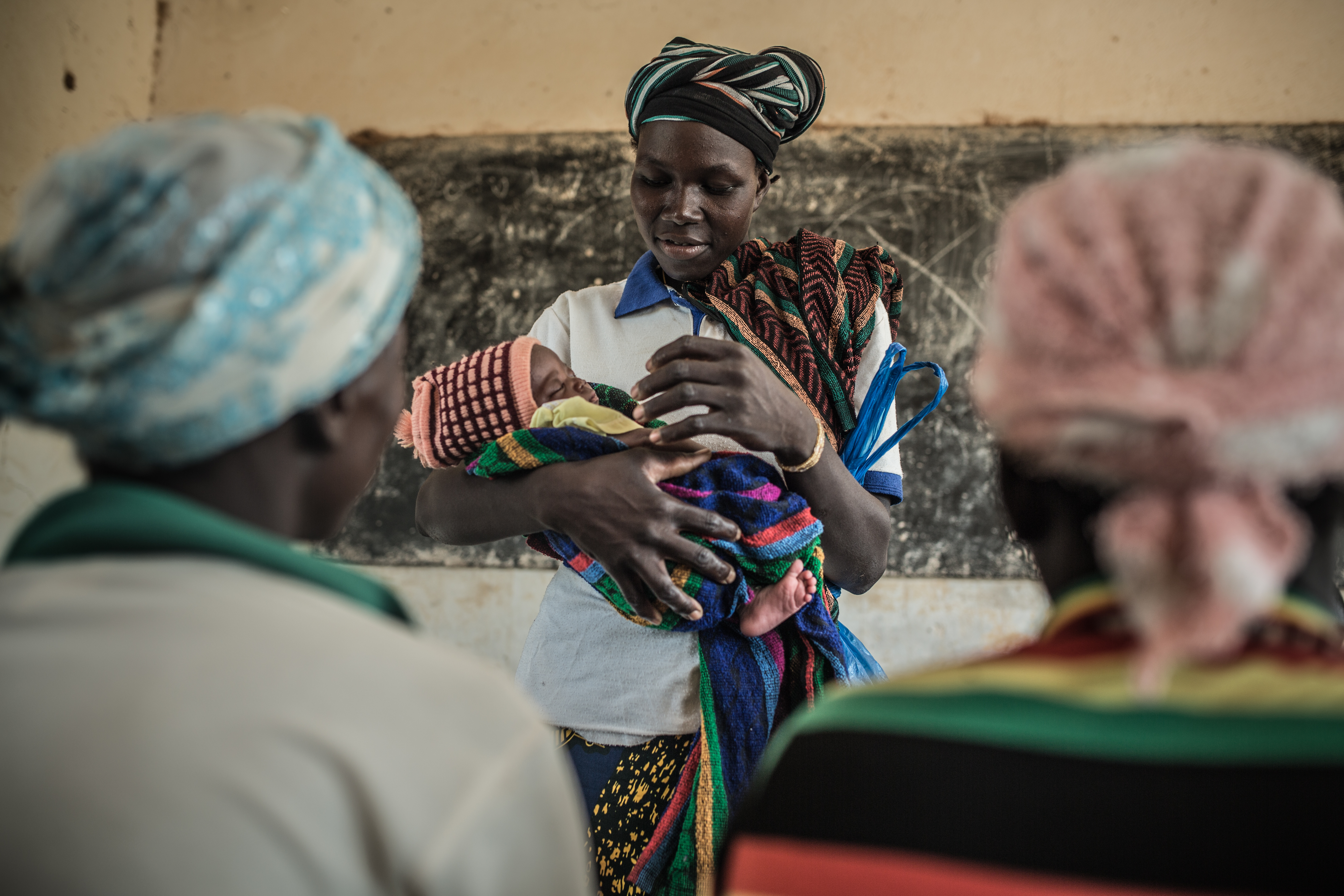 Fati Marmoussa (standing with her son) attends a workshop on preventing malnutrition organized by Oxfam and ATAD, together with other women.