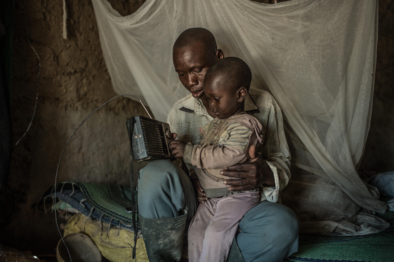 Nabonswendé en compagnie de ses enfants en train d'écouter les prévisions météo à la radio.