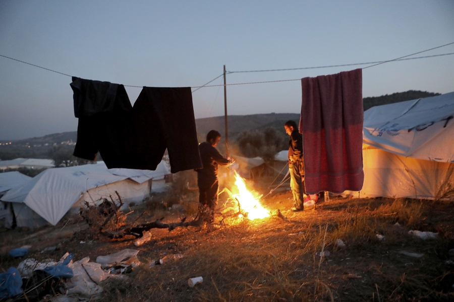 A group of refugees near a fire on the outskirts of the Moria refugee camp, where they set up tents among olive groves awaiting asylum granting.