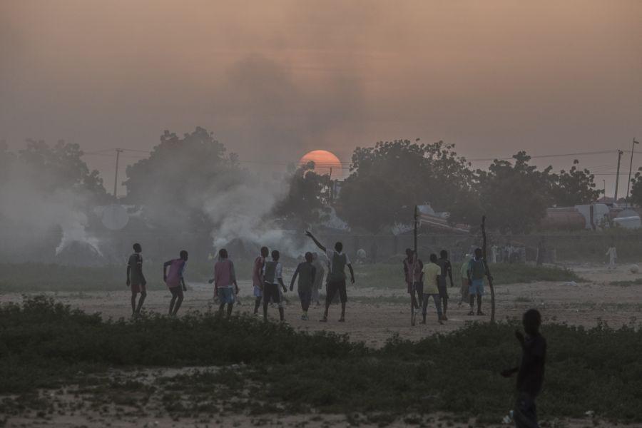 Un grupo de chicos juega al fútbol mientras el sol se pone tras el humo de las hogueras del campo para personas desplazadas en el barrio de Kushari, en Maiduguri (capital del estado de Borno). Foto: Sam Tarling/Oxfam