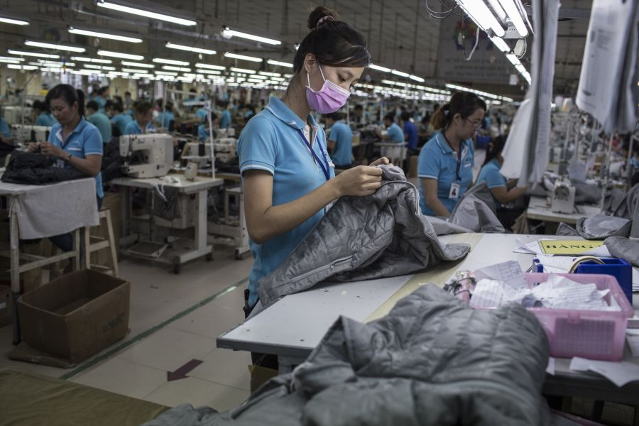 A woman works on a clothing line making winter jackets for an international brand in a garment factory in Dong Nai province, Vietnam, on November 21, 2017.
