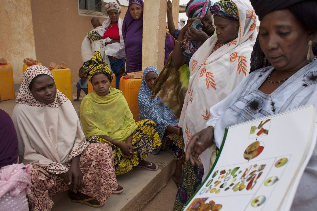 Community health worker ('Relay' volunteer trained by Oxfam) Azara Mohammed using a picture book, at an Oxfam Distribution and Sensitization Session at Azel Treatment Centre, Agadez Region, Niger, March 2015. Photo credit: Abbie Trayler-Smith/Oxfam