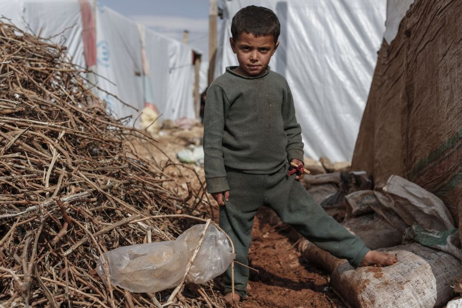 Malik, 7, from Raqqa in Syria, stands barefoot amid the mud, in an informal settlement for Syrian refugees in Lebanon's Bekaa Valley.