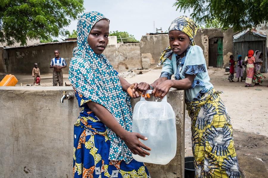 Deux jeunes filles à un point d'eau installé par Oxfam à Maiduguri, près du village de Pulka, dans l'État de Borno. Photo : Tom Saater/Oxfam