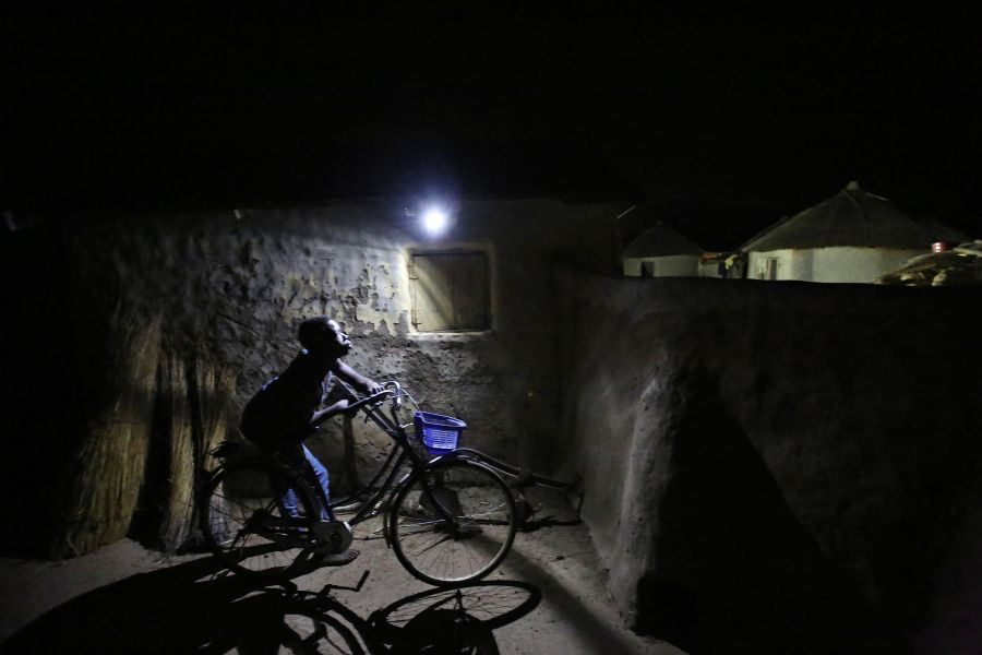 A boy passes by a motion-activated LED light in Kpatua village.