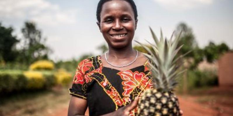 Mukeshimana Leocadie tient un ananas devant la coopérative de Tuzamurane, à l'est du Rwanda, dont elle est l'un des membres.