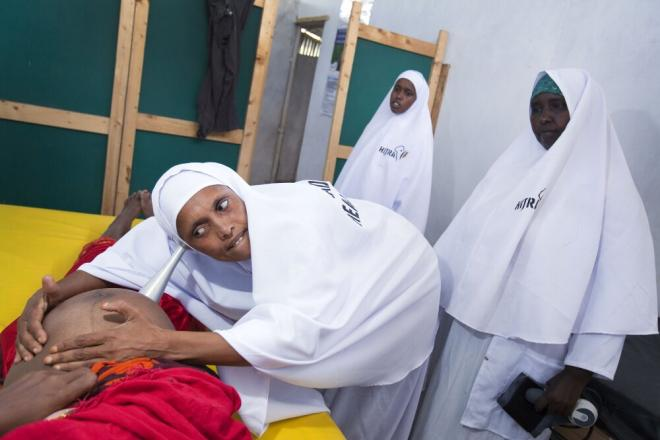 Shukri Abdul-Kadir Ahmed, a nurse at a health center in Badbaado camp, Mogadishu, listens for a baby's heartbeat. Badbaado shelters 28,000 people who have fled conflict or drought. Photo: Petterik Wiggers.