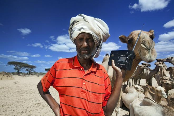 Hussein Mohammed listens to the BBC Somali service on his radio while his camels stop for water. Radio is often the main source of information for people in rural areas. Photo: Petterik Wiggers.