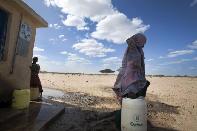A woman is carrying an Oxfam bucket. Photo credit: Petterik Wiggers.