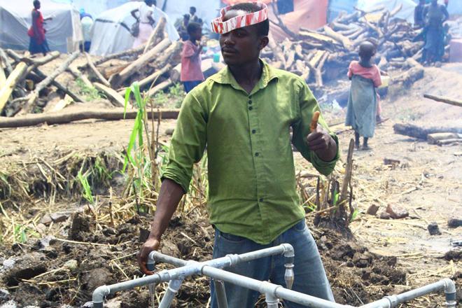 Un volontaire de la Croix-Rouge ougandaise se sert à un point d'eau