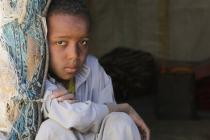 Mohammed (9) sitting in the entrance of a tent in the Huth IDP camp, Amran.