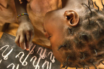 Girl writing letters with chalk on blackboard Burkina Faso