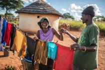 Ulita Mutambo's husband Muchineripi Sibanda helps her hang up laundry outside their home in Ture Village, Zvishevane region, Zimbabwe. Aurelie Marrier d'Unienville / Oxfam