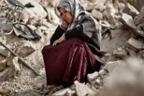 Zakia Abdullah, assise au milieu des ruines, à Alep, Syrie. Photo : Pablo Tosco