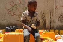 Un garçon attend son tour pour aller chercher de l'eau. Il mendie de la nourriture et mange du pain venant d'une boulangerie voisine.
