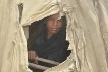 A girl peeps out of her family's tent, Yemen