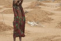 A girl stands amid the graves of 70 children, Dadaab. Photo: Andy Hall/Oxfam