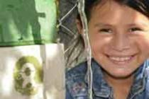 Jeidi Garcia Rivera reçoit de l'eau potable d'un robinet à côté d'une école à El Recuerdo, El Salvador. L'eau vient d'un puit fourni par Oxfam Amérique et ses partenaire local, PROVIDA. Photo: Luis Galdámez/Oxfam America