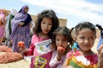 Des enfants mangent des denrées distribuées dans le cadre de l'aide alimentaire aux réfugiés, au Sahara occidental