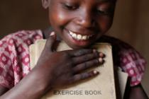 Agnes, 8, proudly holding her school book. Photo: Abbie Trayler-Smith/Oxfam