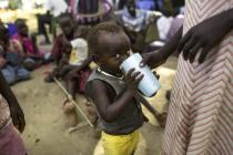 A woman gives a glass of water to a child, in Bor, South Sudan. Photo: Kieran Doherty/Oxfam