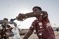 Des enfants se servent à un point d'eau installé par Oxfam dans le camp de Hassansham, en Irak. Crédit: Tegid Cartwright/Oxfam