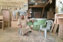 Anwar sits in his furniture workshop in Gaza. Photo: Sami Alhaw/Oxfam