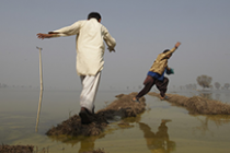 Two men avoid flooded land in fields, Pakistan