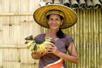 A woman holds up home grown bananas in the Philippines