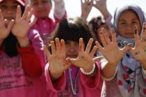 Syrian refugee children in Za'atari camp make the dove symbol of peace