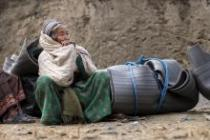 Laxmi Maya, 60, waits with the goods she has received from Oxfam's winter and shelter distribution.