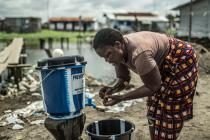 A woman is washing her hands, to prevent Ebola's spread, in Clara Town, Liberia. Photo: Pablo Tosco/Oxfam
