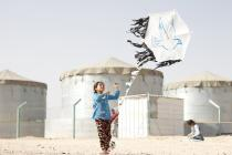 A young girl flies a kite in Za'atari camp. Photo credit: Adeline Guerra/Oxfam
