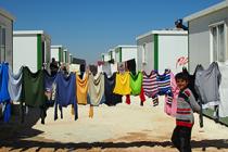 Boy walks past washing line Zaatari Refugee Camp