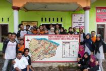Villagers in Belanting, Indonesia, with a map showing the village's risks, emergency meeting points and evacuation routes. A comprehensive, community-based approach is key for successful risk management. Photo: Rodrigo Ordonez/Oxfam