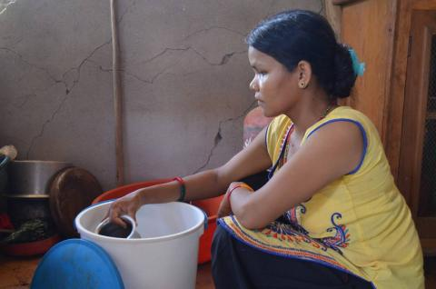 Radhika Majhi, 25, uses a bucket Oxfam provided in Khadgabhanjyang VDC-4 in Nuwakot district. She is now living in a temporary shelter made from CGI sheets and bamboo mats with her husband, in-laws and her five-year-old son. Photo credit: Oxfam
