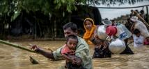 A father carries his son across a broken bridge on the edge of Balhukali camp, Bangladesh. Heavy rains flooded the areas where people had set up temporary shelters, forcing them to move to higher ground. Photo: Aurélie Marrier d'Unienville