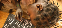 Girl writing letters with chalk on blackboard Burkina Faso