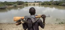Un jeune berger tient un AK-47 sur ses épaules, au Kenya. Photo : Sven Torfinn/Oxfam