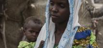 Hassana, 25 ans, du Nigeria, avec sa petite fille de 11 mois devant le petit abri de fortune dans lequel elles vivent, dans le nord-est du Niger.